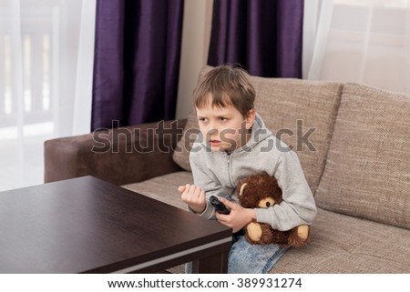 Nervous 7 year old boy child sitting on the sofa and watching tv. Hugs his favorite teddy bear and changing channels by remote control. - stock photo