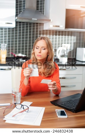 Nervous young caucasian woman looking at her financial debts in the kitchen at home - stock photo