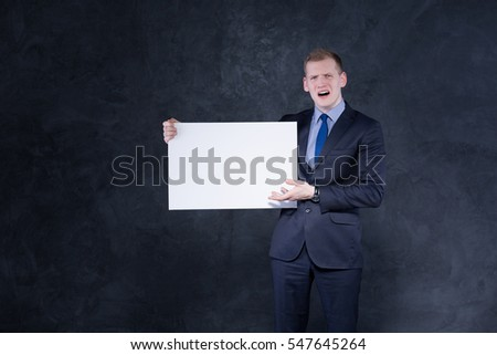 Nervous young man carrying white piece of paper
