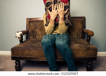 Nervous young man on couch hiding behind cushion