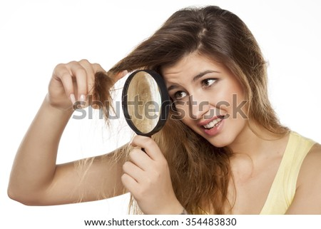 nervous young woman looking at her hair with a magnifying glass - stock photo