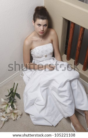 Nervous young woman wearing a wedding gown, sitting on an interior floor.