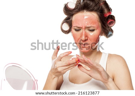 nervous young woman with curlers and a mask on her face clean her nails