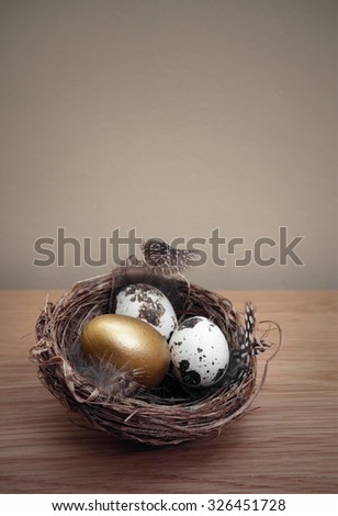 Nest Egg, a golden egg inside a nest on a wooden table with a wall as background copy space - stock photo