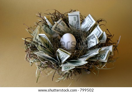 Nest Egg: Money lines the nest of this not-yet-hatched egg against a gold background. - stock photo
