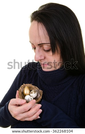 Nest egg. Pension or retirement fund. Woman caring for a nest full of eggs including a golden egg. Portrait on white background - stock photo