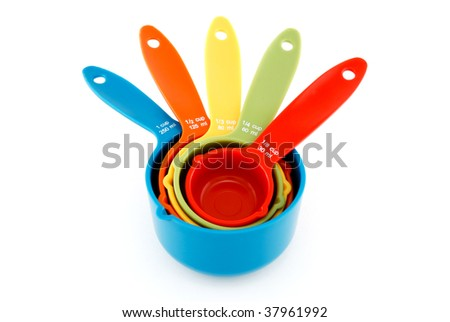 Nested colorful measuring cups isolated on white.