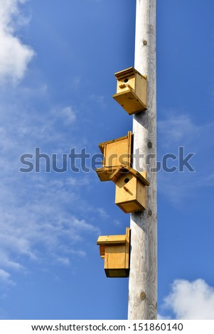 nesting boxes on a column against the blue sky - stock photo