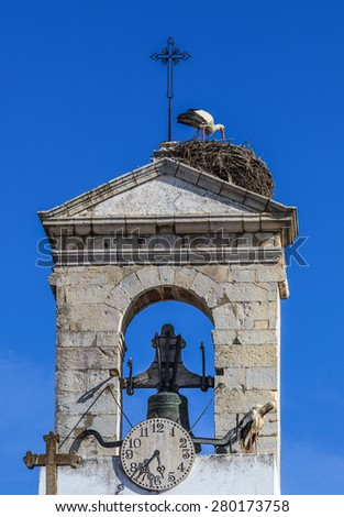 nesting European storks on white cathedral tower.  stork at the top of the church - stock photo