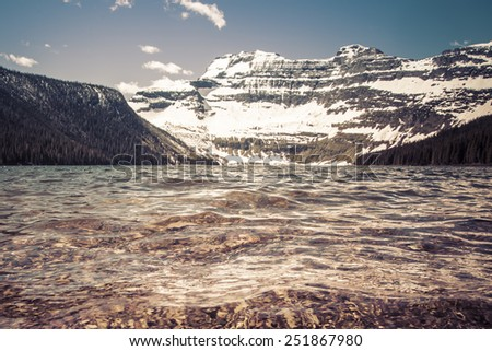 Nestled in a glacial basin, Cameron Lake is a hidden jewel high in the Canadian Rockies.  Part of Waterton Lakes National Park, Cameron Lake offers fishing, hiking trails, boating & breathtaking views - stock photo