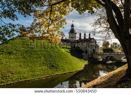 Nesvizh, Belarus - October 13, 2016: Autumn view of Nesvizh castle framed by tree and branches with autumn leaves.