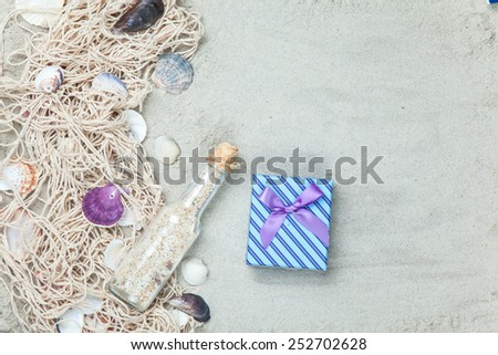 Net, shells with bottle and gift box on sand background. - stock photo