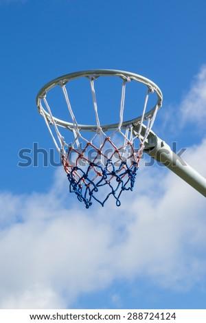 Netball hoop against blue sky - stock photo