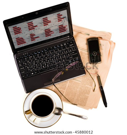netbook with graphics on the screen; standing on the newspaper marked with red pen. Also at the table; pen; glasses and a cup of coffee with two lumps of sugar and a spoon. - stock photo