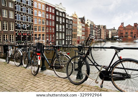 NETHERLANDS. AMSTERDAM - JUNE 23, 2015: Bicycle parking on the quay of the channel on the background of the historic architecture. - stock photo