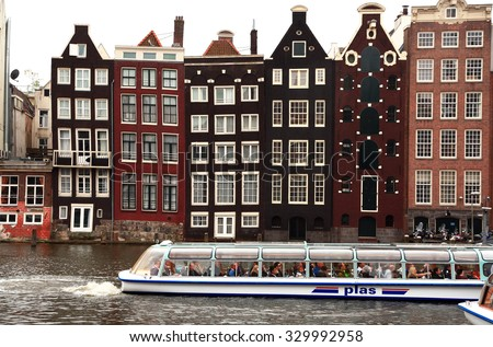 NETHERLANDS. AMSTERDAM - JUNE 23, 2015: Pleasure boat floats on the channel on the background of the beautiful city historic architecture - stock photo