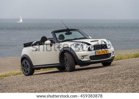 Netherlands July 24, 2016 Mini Coops S convertible standing at a dike at the North Sea  with open roof.