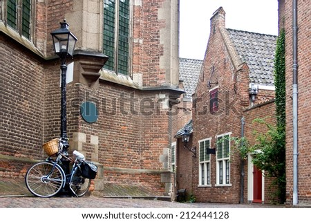 Netherlands - Njmegen - Old historic street with houses made of  brick and a bike bound on a lighting poles.  - stock photo