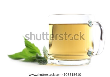 Nettle and freshly made nettle tea in a glass cup isolated on white background. Shallow dof - stock photo