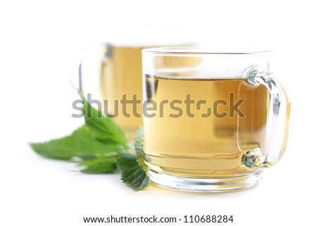 Nettle and freshly made nettle tea in glass cups isolated on white background. Shallow dof - stock photo