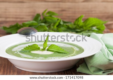 Nettle cream soup with sour cream. Shallow dof - stock photo