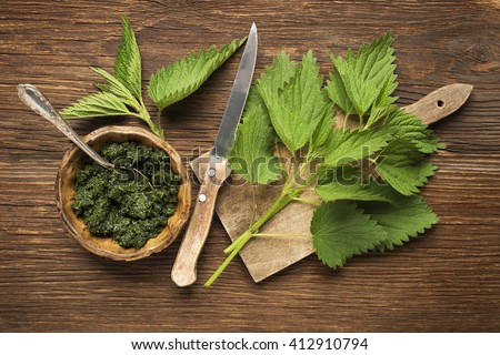 Nettle fresh green leaves on a wooden background. - stock photo