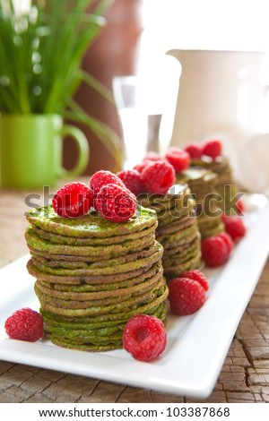 Nettle or spinach pancakes with raspberries - stock photo