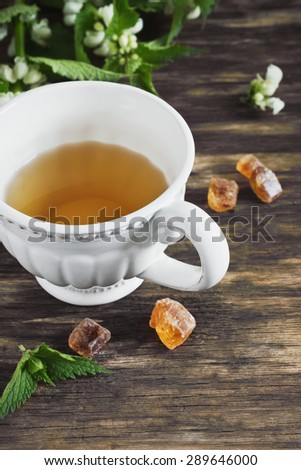 nettle tea and twigs of fresh nettle on the old wooden background. health and diet  beverage - stock photo
