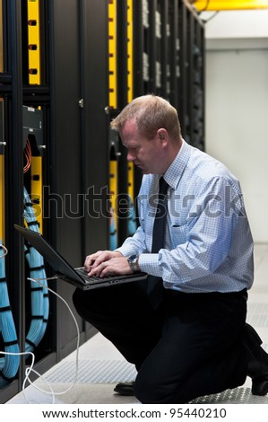 Network administrator is setting up network switches, firewalls and routers using a laptop. - stock photo
