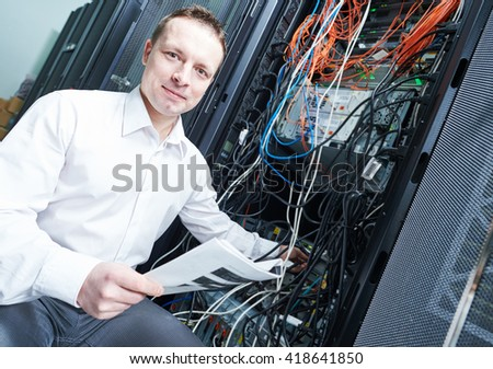network engineer administrating in server room  - stock photo