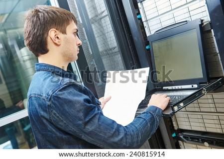 network engineer working in server room - stock photo