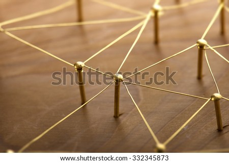 Network, networking, internet communication abstract. Web of gold wires on rustic wood.