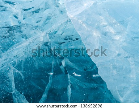 Network of cracks in thick solid layer of ice of a frozen river - stock photo