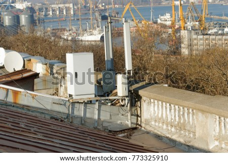 Network repeaters of telecommunication base stations on roof of building. An aerial of cellular communication on roof of building. Telecommunication tower of cell phone. Antennas on roof of building