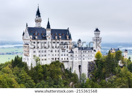 Neuschwanstein, Lovely Autumn Landscape Panorama Picture of the fairy tale castle near Munich in Bavaria, Germany in the morning hours on a foggy day - stock photo