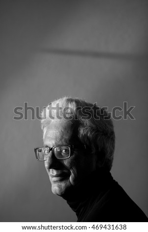 Never get old, handsome and sexy at every age concept. Close up portrait of fashionable mature man wearing trendy eyewear, black turtleneck. Modern haircut. Silver hair. Daylight. Indoor shot