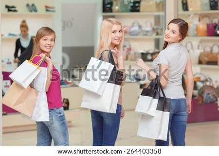 Never stop doing shopping. Three beautiful girls in casual clothes turning back to the camera while holding shopping bags copyspace at the store - stock photo