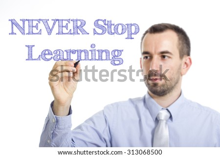 NEVER Stop Learning - Young businessman writing blue text on transparent surface - stock photo