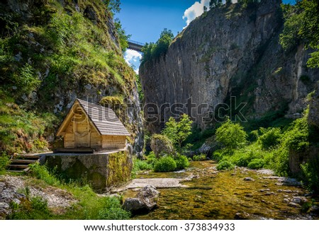 Nevidio canyon. Rock cliff, river, bridge and small wooden house.  Invisible canyon, popular touristic attraction of Montenegro.