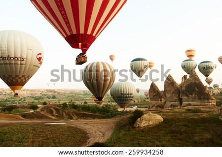 NEVSEHIR, TURKEY - MAY 08, 2012:Colorful hot air balloons flying over rock landscape at Cappadocia. - stock photo