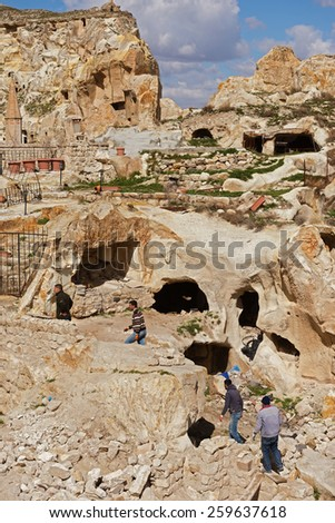 NEVSEHR, TURKEY - MARCH 04, 2015:Cappadocia, Central Anatolia in Turkey. Desert landscape with ancient rock carved houses in Goreme turkish Kapadokya region in Asia Minor.Turkish man working.