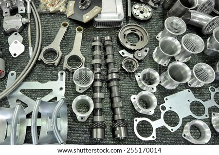 New and shiny part of rally car engine on a table in workshop:  clutch, connecting rod from a car engine, piston, camshaft and more. - stock photo