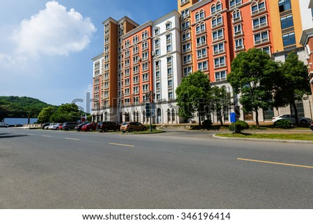 New apartment building in suburban area and the asphalt road - stock photo
