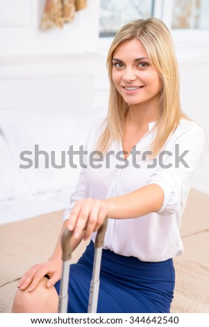 New arrival.  Attractive young woman sitting at the edge of bed in her hotel room.  - stock photo