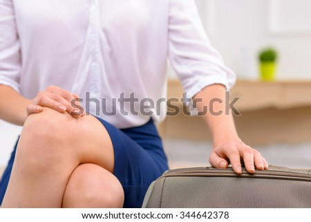 New arrival.  Attractive young woman sitting in her hotel room and watching her luggage.  - stock photo