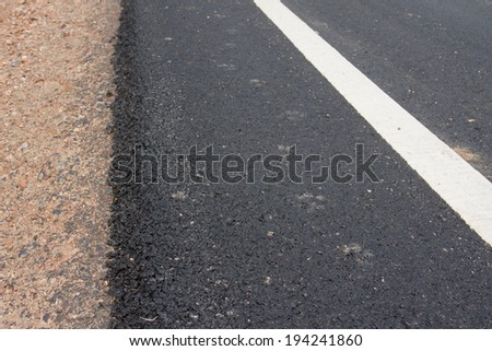 new asphalt road and white curb line, roadside with rock and soil material on new paved street - stock photo