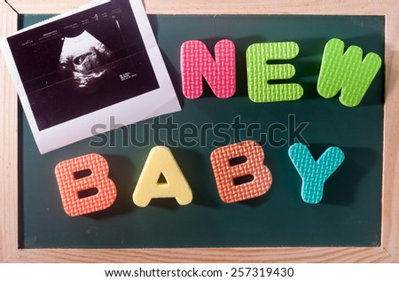 New baby and ultrasound scan picture, conceptual colourful word and image on blackboard - stock photo