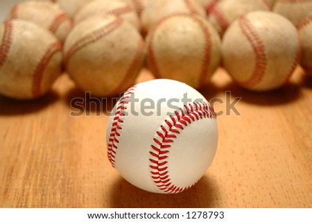 New baseball in front of group of old worn baseballs - selective DOF