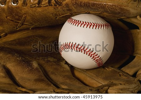 New baseball laying in old worn glove