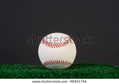 New baseball shot against a black background. - stock photo